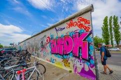 BERLIN TYSKLAND - JUNI 06, 2015: Berlin vit väggmålning med graffitis på sidorna, bycycles som parkerar på gatan Royaltyfri Fotografi