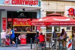 BERLIN TYSKLAND - JUNI 10 2017: En försälja stall med yttersidatabeller av det senaste fastfooddillet i Berlin, arkivbild