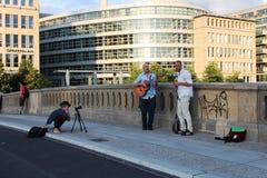 Berlin Tyskland: Musiker och flicka-fotograf på bron i Belin arkivfoton