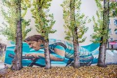 BERLIN TYSKLAND - OKTOBER 29, 2012: Väggmålning i Berlin med Guy Riding Bicycle Royaltyfria Bilder