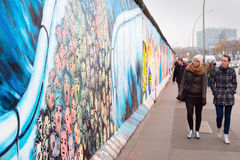 Berlin wall. BERLIN, GERMANY - NOV 15, 2014: People walkingat Berlin Wall at East Side Gallery . It's a 1.3 km long part of original Wall which collapsed in 1989 Stock Photography