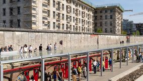 Berlin Wall at the Topography of Terror Documentation Center. BERLIN - APRIL 28, 2018: Tourists walking past a part of the Berlin Wall at the Topography of royalty free stock photos