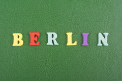 Berlin word on green background composed from colorful abc alphabet block wooden letters, copy space for ad text Royalty Free Stock Photo
