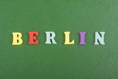 Berlin-Wort auf dem grünen Hintergrund verfasst von den hölzernen Buchstaben des bunten ABC-Alphabetblockes, Kopienraum für Anzei Lizenzfreies Stockfoto