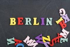 BERLIN-Wort auf dem schwarzen Bretthintergrund verfasst von den hölzernen Buchstaben des bunten ABC-Alphabetblockes, Kopienraum f Lizenzfreie Stockfotografie