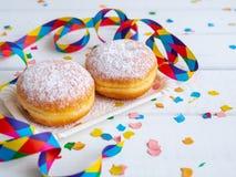 Berliner doughnut op een een document plaat en Carnaval-decoratie stock foto