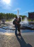 Berlino, Germania, il 19 maggio 2018 una coppia amorosa rappresenta una grande fontana accesa dal sole di sera Fotografie Stock Libere da Diritti