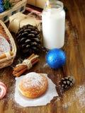 Berlinois de butées toriques et un verre de lait entouré par des attributs de Noël image libre de droits