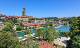 Bern cityscape. Bern, Switzerland - summertime cityscape with the Aare river and the Berner Munster cathedral, which tower is under the restoration royalty free stock photo