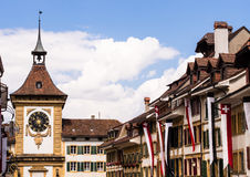 Bern Gate in Murten, Switzerland. Clock tower on the the Bern Gate next to historic buildings on Hauptstrasse in Murten (Morat). Fribourg, Switzerland royalty free stock photo