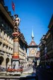 BERN SCHWEIZ - MAJ 26, 2017: En härlig springbrunn och det berömda astronomiska klockatornet på den medeltida staden av Bern Royaltyfri Bild