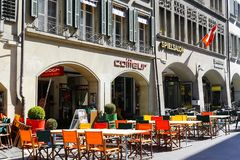 Colorful chairs of outdoor restaurant. Bern, Switzerland - April 21, 2017: Colorful chairs of outdoor restaurant there are also rectangular tables on a sidewalk Stock Photo