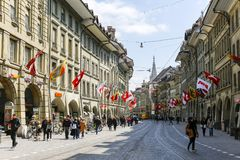 Townhouses decorated with many various flags. Bern, Switzerland - April 20, 2017: Tenement houses along the street of the old town were decorated with many royalty free stock photos