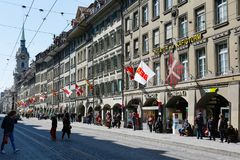 Townhouses and visible flags along a street. Bern, Switzerland - April 20, 2017: Townhouses and flags are visible along the street on which you can see the tram Royalty Free Stock Photo