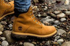 Bern, Switzerland,9.12.18: Almost ready. Close up of stylish yellow boot on female leg. Lady standing on the grass royalty free stock photography