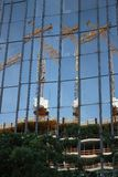 berna 06/14/2008 Πρόσοψη γυαλιού ενός κτηρίου με την αντανάκλαση ενός εργοτάξιου οικοδομής Γερανοί και υλικά σκαλωσιάς στοκ εικόνες