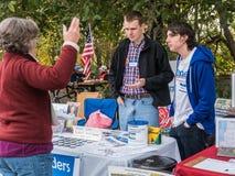 Bernie Sanders-de vrijwilligers spreken met vrouw bij de informatie van de Landbouwersmarkt stock fotografie