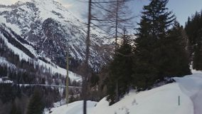 The Bernina Express Red Train passing through the Alps. The Bernina Express Red Train through the Alps in Winter stock footage