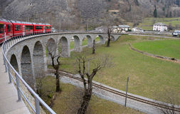 Bernina express train in brusio ring. The red train between Tirano, Italy, and sankt Moritz in switzerland the typical  bridge in brusio Royalty Free Stock Photography