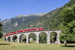 Bernina Express train is going through the famous circular viaduct Royalty Free Stock Image