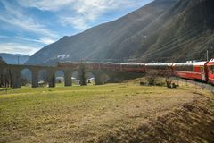 Bernina Express train riding down the famous Brusio spiral viaduct. Alp Grum, Switzerland - February 16, 2019: Bernina Express train riding down the famous stock images