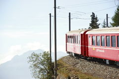 Bernina railway. Crossing the boarder between Switzerland and Italy a smart landscape is crossed by a red nice train Stock Photo