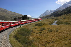 Bernina railway. Crossing the boarder between Switzerland and Italy a smart landscape is crossed by a red nice train Stock Photos
