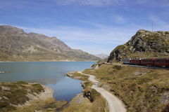 Bernina railway. Crossing the boarder between Switzerland and Italy a smart landscape is crossed by a red nice train Royalty Free Stock Images