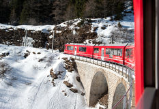 Bernina red train climbing in the snow, view from window Royalty Free Stock Photography