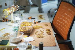 Bernsteinfarbig Der Prozess der Herstellung bördelt vom sunstone mithilfe des Threads und der Nadel lizenzfreie stockbilder