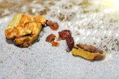 Bernsteinfarbig die Stücke des Bernsteines im Sand auf dem Strand stockbilder