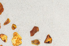 Bernsteinfarbig die Stücke des Bernsteines im Sand auf dem Strand stockfotos