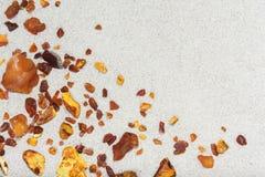 Bernsteinfarbig die Stücke des Bernsteines im Sand auf dem Strand lizenzfreies stockbild