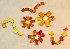Bernsteinfarbige Blumen auf der Textiloberfläche Stockfotografie