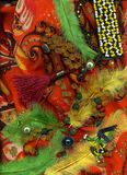 Bernsteinfarbige Perlen, die auf buntem Schal mit Knöpfen und Federn liegen stockfoto