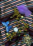 Bernsteinfarbige Perlen, die auf gestreiftem Stoff mit Knöpfen und Stichdesignen liegen Lizenzfreies Stockfoto