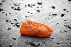 Bernsteinfarbiger Stein auf dem Strand Kostbarer Edelstein, Schatz Stockbilder