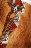 Bernsteinfarbiges Armband auf Stein lizenzfreie stockfotos