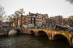 Beroemde uitstekende gebouwen & kanalen van de stad van Amsterdam bij zonreeks Algemene landschapsmening Stock Afbeelding