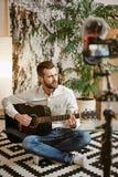 Beroemde zanger Gebaarde mannelijke de gitaar spelen en muziek die blogger, terwijl het registreren van nieuwe video voor zijn ab stock foto's