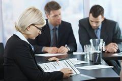 Beroeps die documenten controleren op vergadering stock fotografie