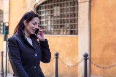 Beroeps die uitvoerende vrouwenbesprekingen charmeren door cellphone Stock Foto