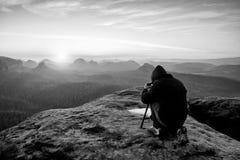 Beroeps op klip De aardfotograaf neemt foto's met spiegelcamera op piek van rots Stock Afbeelding