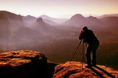 Beroeps op klip De aardfotograaf neemt foto's met spiegelcamera op piek van rots Dromerig blauw fogy landschap, Royalty-vrije Stock Foto's