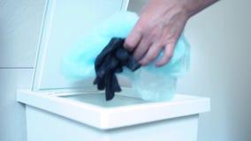 Beroepsbeoefenaar die weg beschikbare latexhandschoenen in afval werpen voorraad Besmettelijk afval in zak in het ziekenhuis stock footage