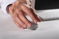 Beroepstendinitis ziekteconcept: de mens die bij computer werken masseert zijn juiste vuist stock fotografie