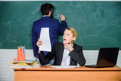 ?berpr?fen Sie Hausarbeit Notieren Sie Ihre Aufgabe Lehrer, die im Paarschulklassenzimmer arbeiten Schulerzieher und Lehrerauszub lizenzfreies stockbild