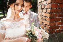 ?berraschende Hochzeitspaare H?bsche Braut und stilvoller Br?utigam nahe der Kirche stockbilder
