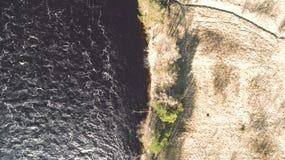 ?berraschender Luftschu? des sch?nen dunklen Flussufers Herbstrandauslegung mit Eicheneicheln und -tageslicht stockfotografie