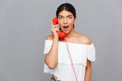 Überraschte Frau, die auf dem Telefonrohr spricht Lizenzfreies Stockfoto